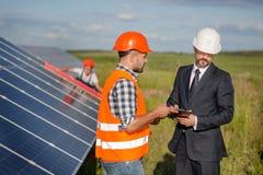 Контракт бизнесмена подписывая с мастером, панелями солнечных батарей техника рассматривая на фоне Стоковые Изображения