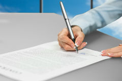 Контракт женщины подписывая около окна Стоковое Фото