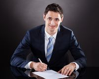 Контракт молодого бизнесмена подписывая на столе Стоковое Изображение RF