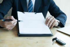 Контракт на продажу подписания бизнесмена присутствующий с ключом автомобиля к custo Стоковое Изображение