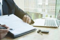 Контракт на продажу подписания бизнесмена присутствующий с ключом автомобиля к custo Стоковое Изображение RF