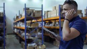 Контролер говоря на телефоне стоя на запачканной предпосылке склада видеоматериал
