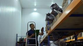 Контролер двигая вверх лестницу и проверяет коробки на верхних полках в хранении видеоматериал