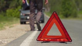 Контролер приходит к автомобилю с аварийными освещениями сток-видео