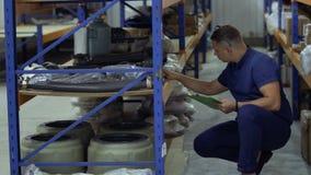 Контролер проверяя детали машинного оборудования в хранении сток-видео