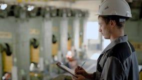 Контролер рассматривая работники завода во время работы, писать вниз результаты видеоматериал