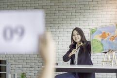 Контролируйте женский аукцион, улыбку и поднимайте фото рыбки к покупщикам которые поднимают значок, с белой предпосылкой кирпича стоковое изображение rf