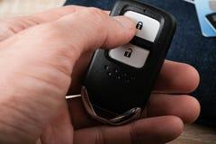 Контролируйте удаленный ключ держа в руке Стоковые Фото
