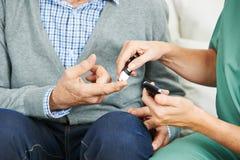 Контроль содержания глюкозы в крови на пальце стоковое изображение