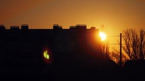 Контуры городского пейзажа зданий мульти-этажа города на заходе солнца рассвет утра солнце смотрит вне от за дома видеоматериал