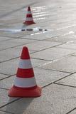 2 конуса движения с красными и белыми нашивками на вымощенном острословии дороги Стоковые Изображения RF