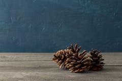 3 конуса сосны закрывают вверх на деревянном столе Стоковое Изображение