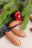 Конусы ели, шарик рождества и зеленые ветви ели Стоковая Фотография RF