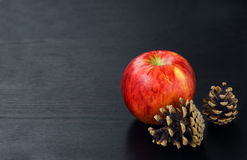 Конусы и яблоко сосны на черной деревянной предпосылке Стоковая Фотография RF