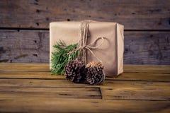 Конус подарочной коробки, ели и сосны на деревянном столе Стоковые Изображения