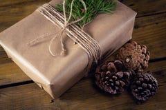 Конус подарочной коробки, ели и сосны на деревянном столе Стоковые Фото