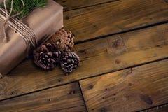 Конус подарочной коробки, ели и сосны на деревянном столе Стоковая Фотография RF