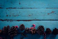 Конус сосны и тросточка конфеты аранжировали на деревянной планке Стоковая Фотография RF