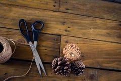 Конус сосны, scissor и продевает нитку на деревянном столе Стоковые Изображения