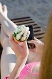 Конус с мороженым в руке девушки в купальном костюме, умный телефон в другой руке Стоковые Изображения RF