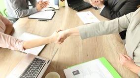 Конференц-зал, 2 команды дела сидя на таблице, будет партнером трясти руки сток-видео