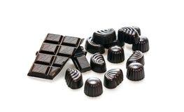 Конфета и сломленные ломти бара темного шоколада стоковое изображение