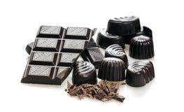 Конфета и сломленные ломти бара темного шоколада стоковые фотографии rf
