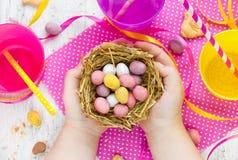 Конфета пасхального яйца в гнезде в руках ребенка Стоковая Фотография RF