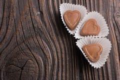 Конфета шоколада в форме сердц на деревянной предпосылке Стоковые Фотографии RF