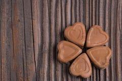 Конфета шоколада в форме сердц на деревянной предпосылке Стоковое Изображение