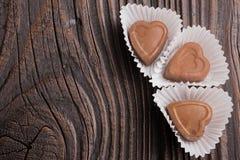 Конфета шоколада в форме сердц на деревянной предпосылке Стоковая Фотография RF
