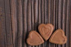 Конфета шоколада в форме сердц на деревянной предпосылке Стоковая Фотография