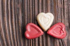 Конфета шоколада в форме сердц на деревянной предпосылке Стоковое Фото