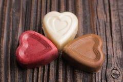 Конфета шоколада в форме сердц на деревянной предпосылке Стоковые Фото