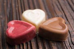 Конфета шоколада в форме сердц на деревянной предпосылке Стоковое фото RF