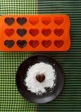 Конфета шоколада в форме сердц на коричневой плите с порошком сахара и bakin формируют с шоколадами против проверенной зеленым цв Стоковое Фото