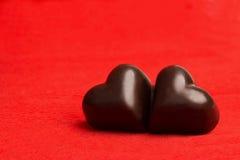 2 конфеты в форме сердца на красном цвете Стоковая Фотография