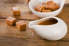 Конфеты и соус карамельки на деревенском деревянном столе Стоковое Изображение RF