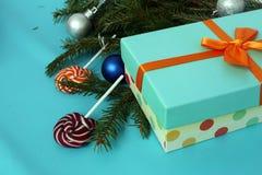 Конфеты рождества на голубой предпосылке с подарком Ветви ели Стоковое Изображение