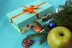 Конфеты рождества на голубой предпосылке с подарком Ветви ели Стоковая Фотография
