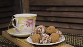 Конфеты шоколада и набор чая на деревянном столе Набор чая фарфора на деревянной предпосылке видеоматериал