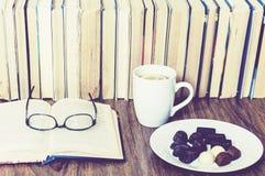Конфеты шоколада на белых плите и чашке чаю с лимоном со стогом книг на предпосылке стоковое изображение rf