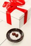 2 конфеты шоколада в форме сердц на коричневой плите рядом с подарочной коробкой с красной лентой против деревянной предпосылки Стоковые Изображения RF
