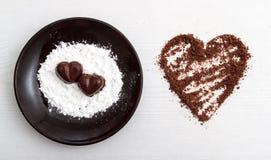 2 конфеты шоколада в форме сердц на коричневой плите с порошком сахара рядом с обломоками шоколада аранжировали в форму сердца Стоковая Фотография RF