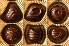 Конфеты шоколада различных форм в коробке золота, взгляд сверху, s Стоковое Изображение