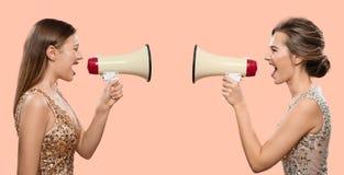 Конфликт Женщины кричат в мегафоне на одине другого стоковые изображения rf