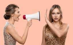 Конфликт Одна женщина кричит в мегафон на другой женщине стоковая фотография rf