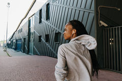 Конца-вверх взгляд назад афро-американского подростка в наушниках идя вдоль улицы Стоковые Фотографии RF