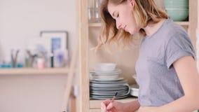 Концентрация женщины художника делая эскиз к сидя домашняя сток-видео