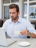 Концентрировать бизнесмена работая с компьтер-книжкой на таблице Стоковое Фото